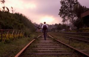 man walking on train tracks